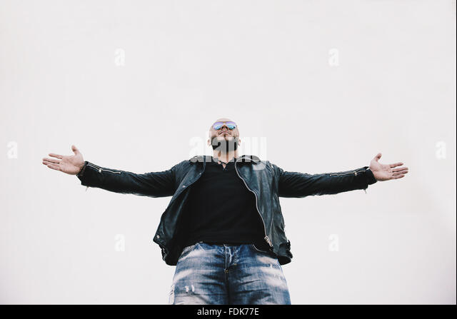 Low angle view of a cool man with arms outstretched - Stock-Bilder