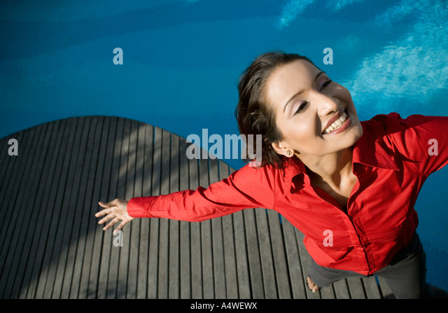 Businesswoman standing by swimming pool with arms outstretched - Stock-Bilder