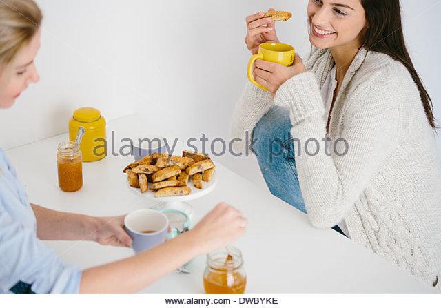 Women having honey drink and biscuits - Stock-Bilder