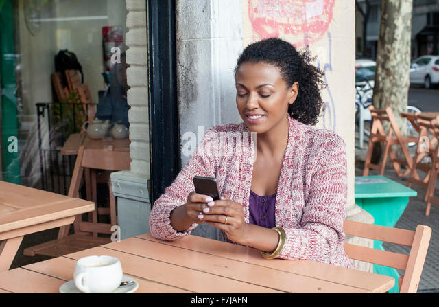 Woman using cell phone at sidewalk cafe - Stock-Bilder