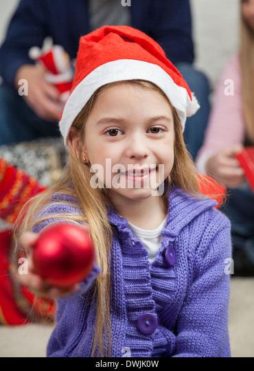 Smiling Girl Showing Christmas Ornament - Stock Image