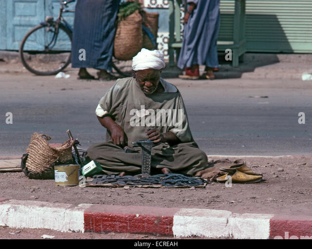 MARRAKECH, MOROCCO – AUGUST, 1979: A craftsman with djellaba and turban, repairs horseshoes sitting in the middle - Stock Image