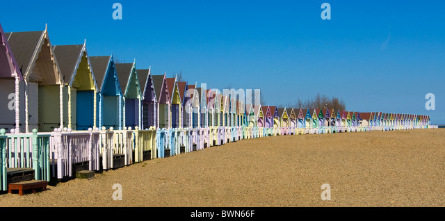 Pastel Beach Huts stretch across a beach in an arc - Stock Image
