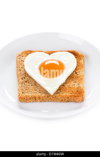 heart shaped cooked egg on toast to illustrate valentines day breakfast or cholesterol health message - Stock Image