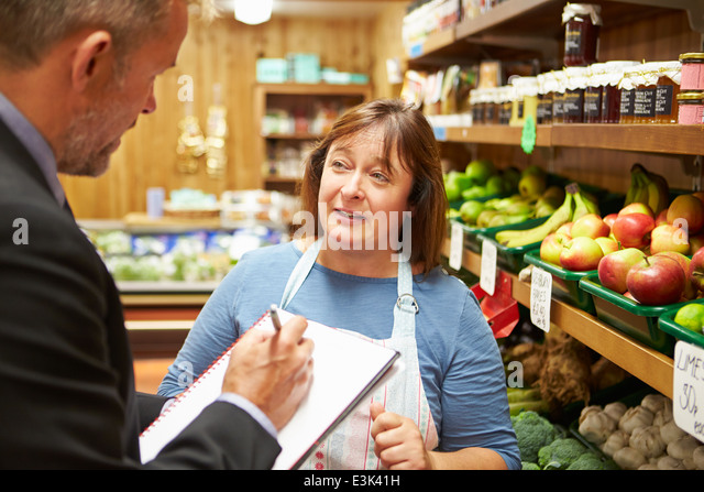 Bank Manager Meeting With Female Owner Of Farm Shop - Stock Image