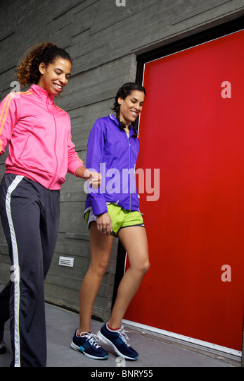 Two girlfriends walking together right after their run in San Diego. - Stock Image