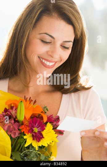 Woman holding flowers and reading note smiling - Stock Image