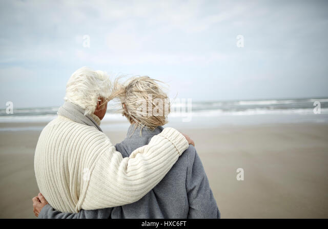 Pensive senior couple hugging and looking at ocean view on windy winter beach - Stock Image