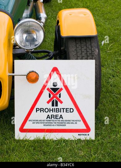 A Spectators Prohibited notice used in motor sport against the front wheel of a yellow Caterham 7 sports car - Stock Image