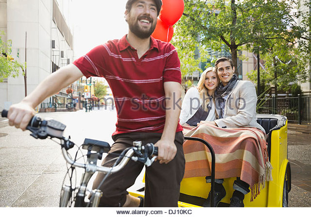 Rickshaw driver and couple on city street - Stock Image