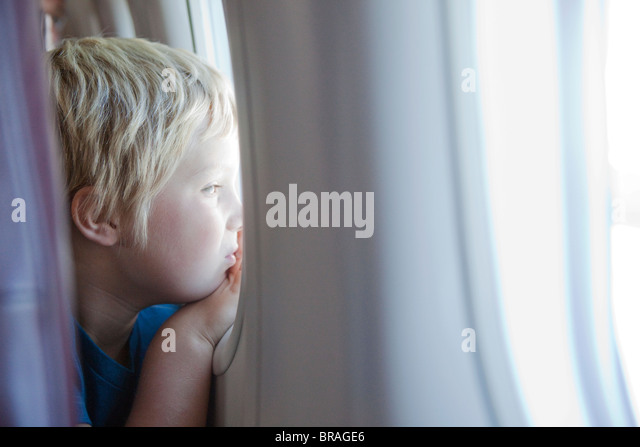 Young boy staring out plane window - Stock Image