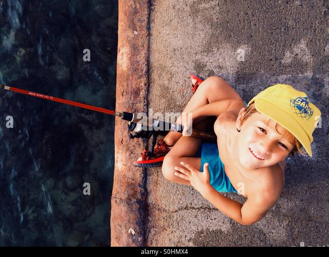 Boy fishing on a harbour - Stock Image