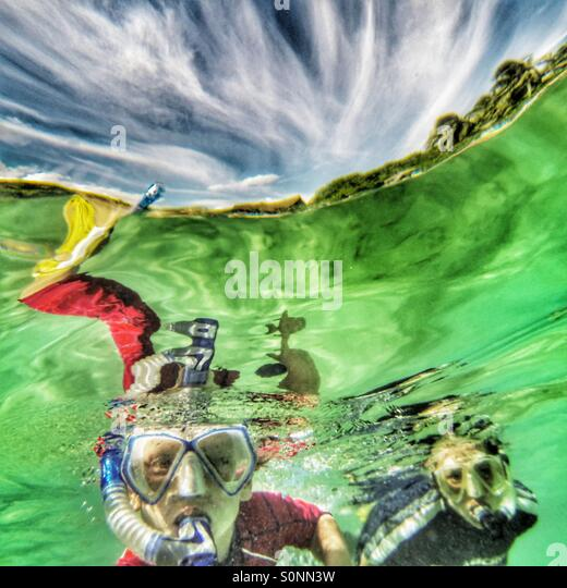 Boy snorkelling with his Mum - Stock Image