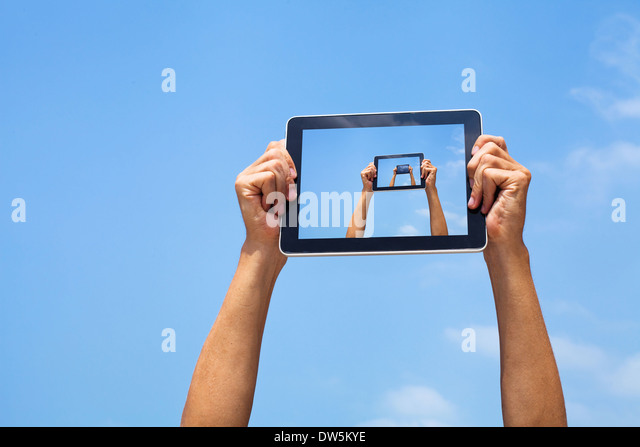 hands holding tablet in blue sky - Stock Image