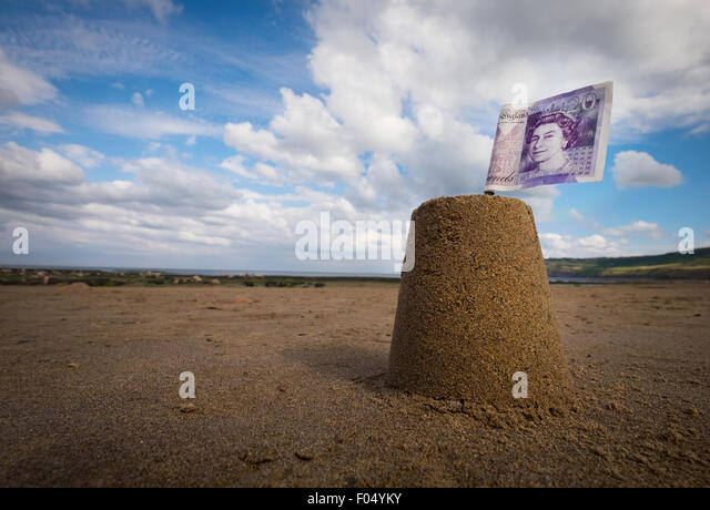 Concept photo of a sandcastle with a £20 note flag on a UK beach to illustrate the cost of School Holidays - Stock Image