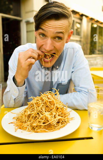 Young man eating skinny french fries at sidewalk cafe - Stock-Bilder