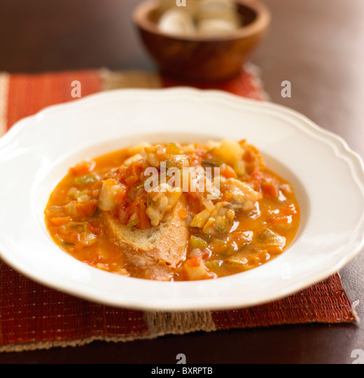 Chunky potato and clam soup with crusty bread - Stock Image