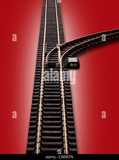 Model train railroad track with a switch and a branch of track curving to the right. Switch has red & green - Stock Image