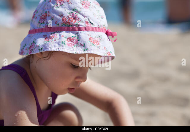 Girl playing on the beach - Stock Image