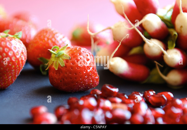 Red fruits and vegetables: strawberries, radish and pomegranate - Stock Image