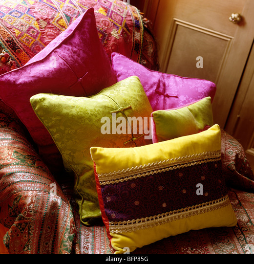 Sofa with Indian cover and bright silk cushions - Stock Image