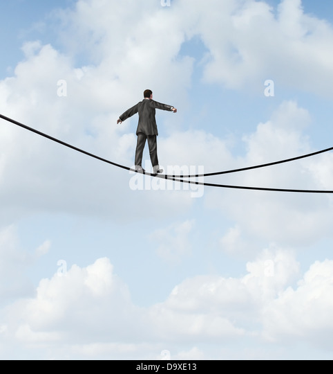 Risky choice business concept with a man walking a dangerous high wire tightrope that is in a crossroads splitting - Stock Image
