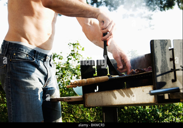 Guy barbequing - Stock Image