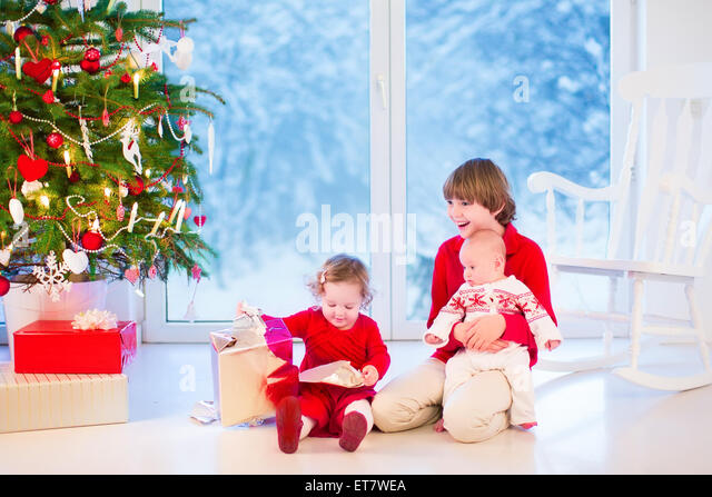 Three kids opening Christmas presents, enjoying Xmas morning in a living room with decorated tree and window into - Stock Image