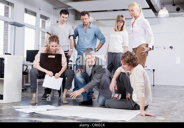 Germany, Bavaria, Munich, Men and women discussing in office - Stock Image