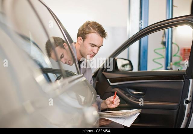 Mechanic examining car in garage - Stock Image