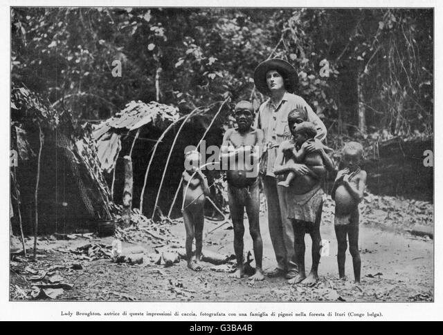 A family of pygmies from the  Ituri forest in the Belgian Congo, photographed with an English visitor, Lady  Broughton - Stock-Bilder