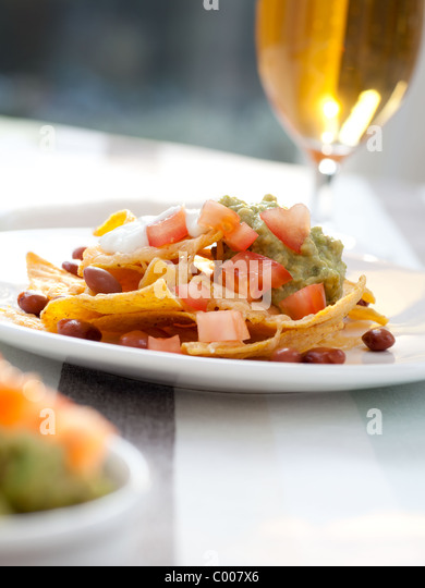 Fresh nacho chips with beans, tomatoes, cheese and guacamole - Stock Image