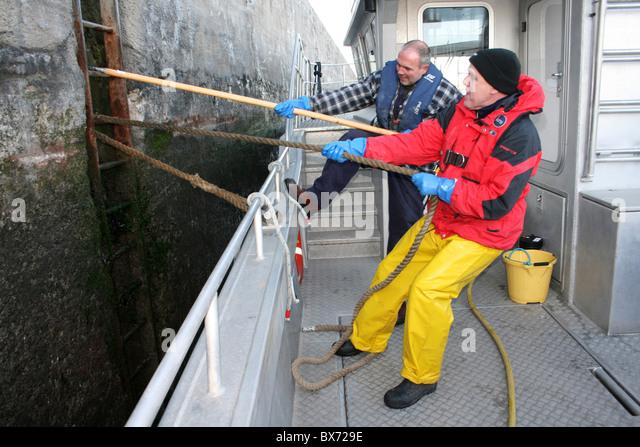 Sailors Tying Up Boat To A Mooring Ladder In Langton Lock, Liverpool Docks, Merseyside - Stock Image