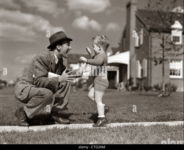 1940s FATHER GREETING SON RUNNING TOWARDS HIM ON SIDEWALK - Stock Image