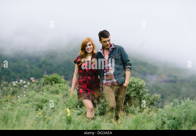Romantic Couple Holding Hands While Walking Through Foggy Field - Stock-Bilder