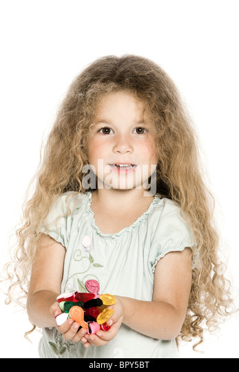 caucasian little girl handfuloffering candies cheerful isolated studio on white background - Stock Image