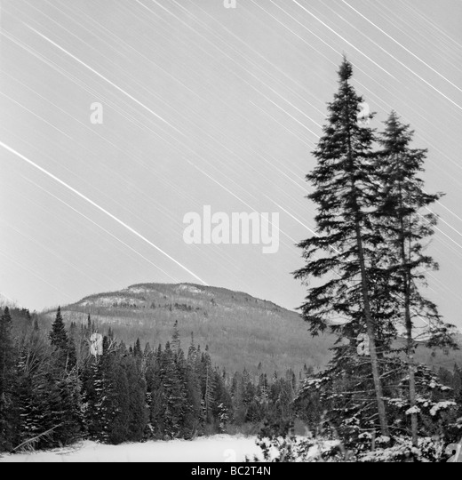 Winter landscape at night with star tracks over the sky - Stock Image