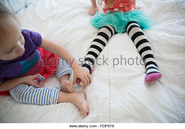 Sisters in striped leggings on bed - Stock Image