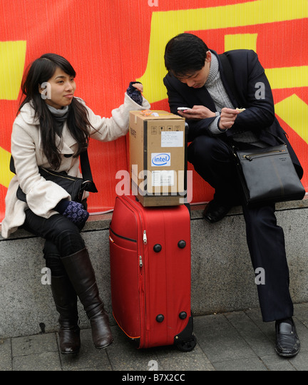 A man checks his mobile phone while waiting to leave the train station of Nanchang, Jiangxi, China. 05-Feb-2009 - Stock-Bilder
