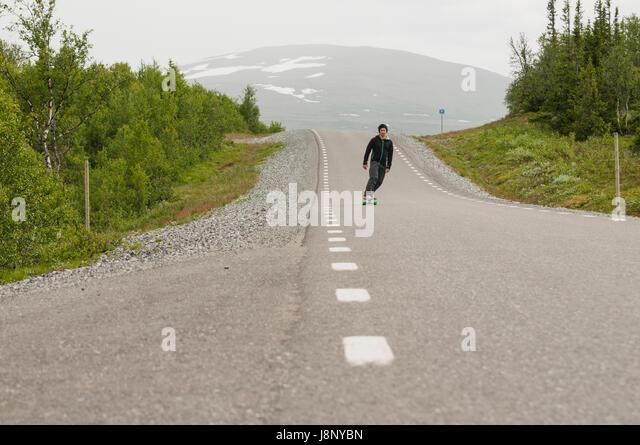 Man skateboarding on road - Stock-Bilder
