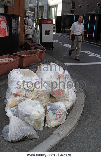 Japan Tokyo Ikebukuro bags bagged trash street corner Asian man - Stock Image