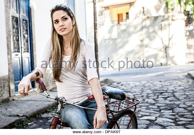 Young couple on bicycle in cobbled street, Rio de Janeiro, Brazil - Stock Image