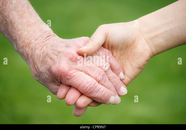Senior lady and young woman holding hands - Stock Image