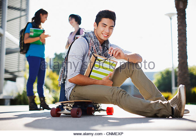 Student sitting on skateboard outdoors - Stock Image