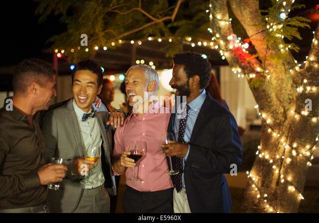 Men talking at party - Stock Image