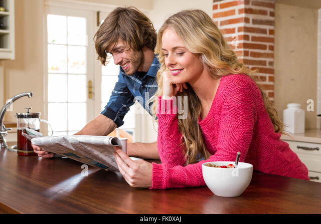 Cute couple reading the newspaper - Stock Image