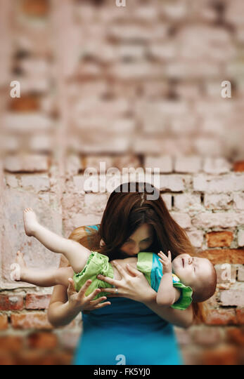 Portrait of Loving Young Mother Holding and Kissing Her Baby against Brick Wall. Selective Focus, Tilt Shift Blurred - Stock Image