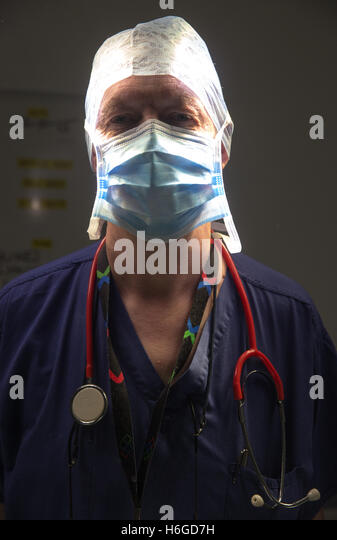 A hospital surgeon in a theatre just prior to an operation with moody lighting - Stock Image