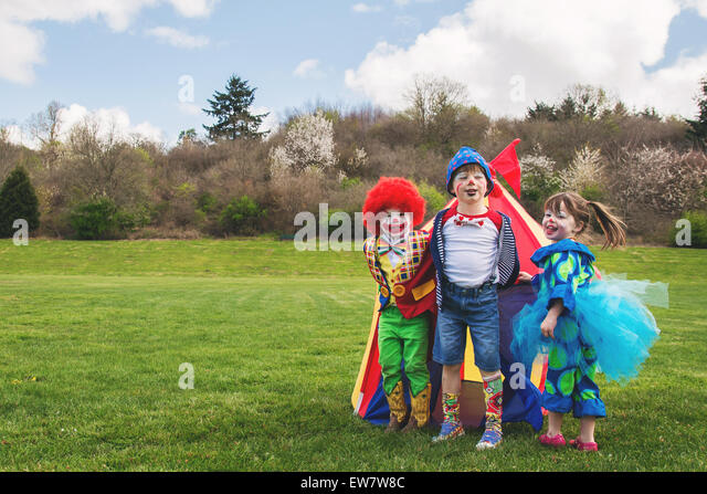 Three smiling children dressed as clowns - Stock Image