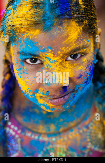 Young Indian girl covered in coloured powder pigment - Stock-Bilder